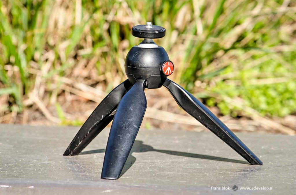 An intensively used Manfrotto Pixi mini tripod on a stony surface in the sun