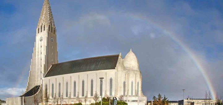 Een regenboog achter de Hallgrimskirkja, de iconische kerk in het centrum van Reykjavik, IJsland