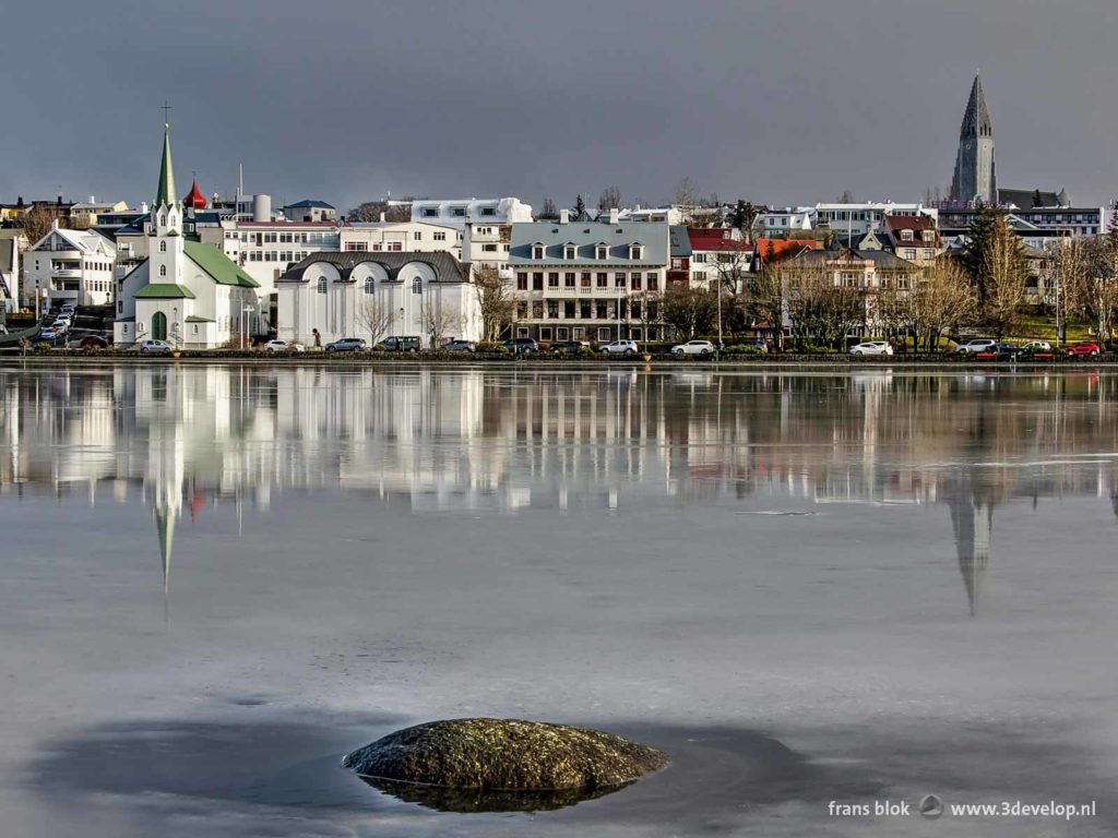 Two churches, Hallgrimskirkja en Frikirkja, reflect in the melting ice of lake Tjornin in Reykjavik, Iceland, at the end of winter