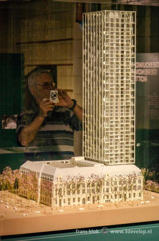 A visitor makes a photo of the cardboard model of the project for the Post Office at Coolsingel in Rotterdam, at an exhibition in that same Post Office