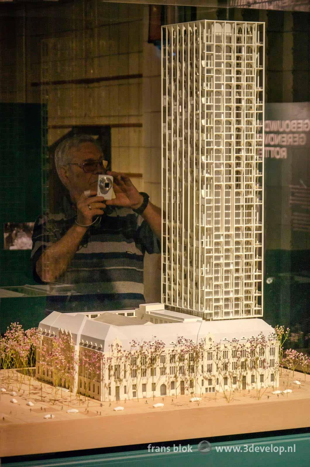 Een bezoeker maakt een foto van de nieuwbouw op het Postkantoor aan de Coolsingel in Rotterdam, op een tentoonstelling in datzelfde Postkantoor.