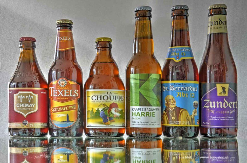 Zes flesjes speciaalbier, Chimay, Texels, La Chouffe, Kaapse Harrie, St. Bernardus en Zundert, gerangschikt volgens de kleuren van de regenboog