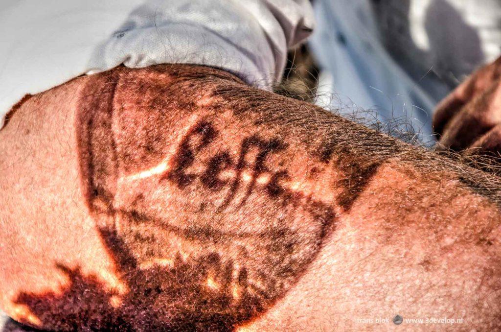 """Een """"tatoeage"""" op een harige onderarm veroorzaakt door zonlicht dat door een Leffe-glas schijnt"""