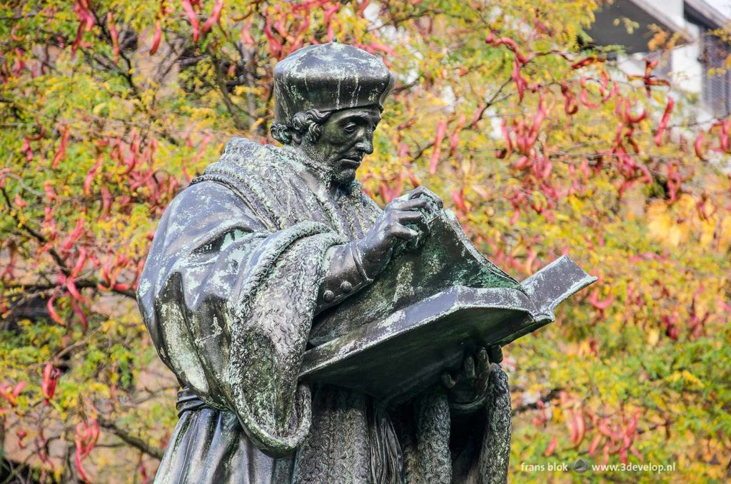 The bronze statue of Desiderius Erasmus in Rotterdam , The Netherlands, surrounded by honey locusts (gleditsia triacantos) with red seed pods and green and yellow leaves