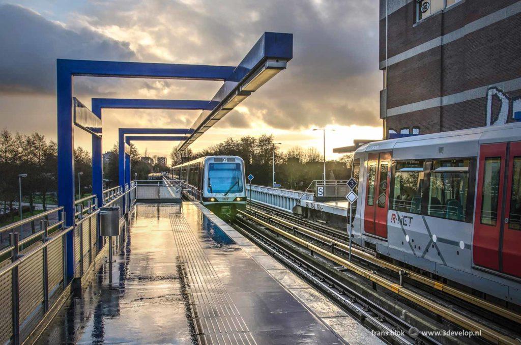 Metrostation Hoogvliet met een stilstaande metro en een metro die aan komt rijden, bij regenachtig weer