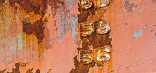 Details of a ship hull with peeling paint, rust stains and stripes and embossed numbers of the draught mark