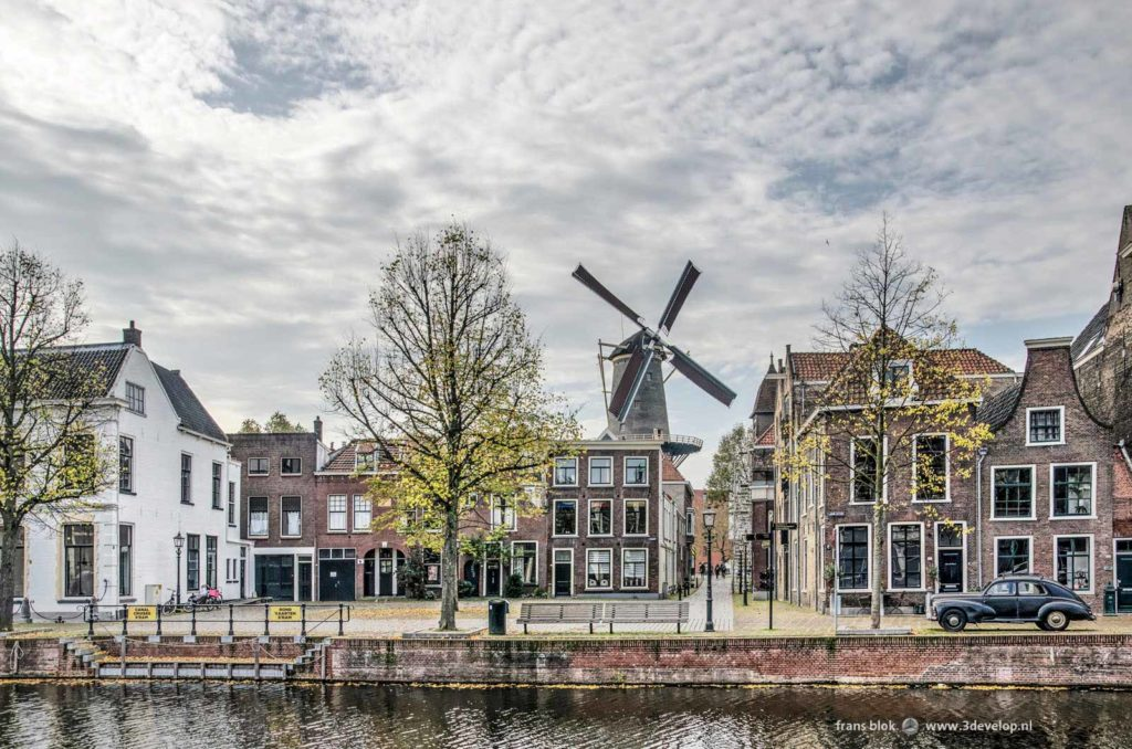 Picture like from a film set with the Long Harbour and the Fish Market in Schiedam, the Netherlands, windmill de Walvisch mill and an old black Peugeot