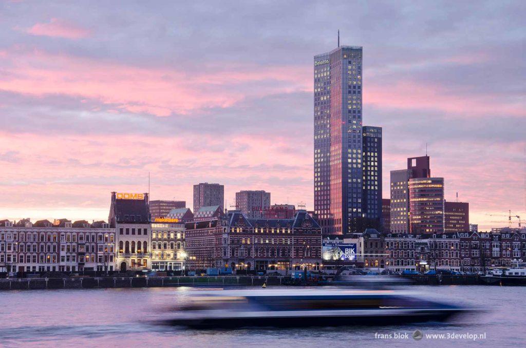 Ochtendgloren boven de Nieuwe Maas in Rotterdam, met de Maastoren, het Noordereiland en een voortsnellende waterbus