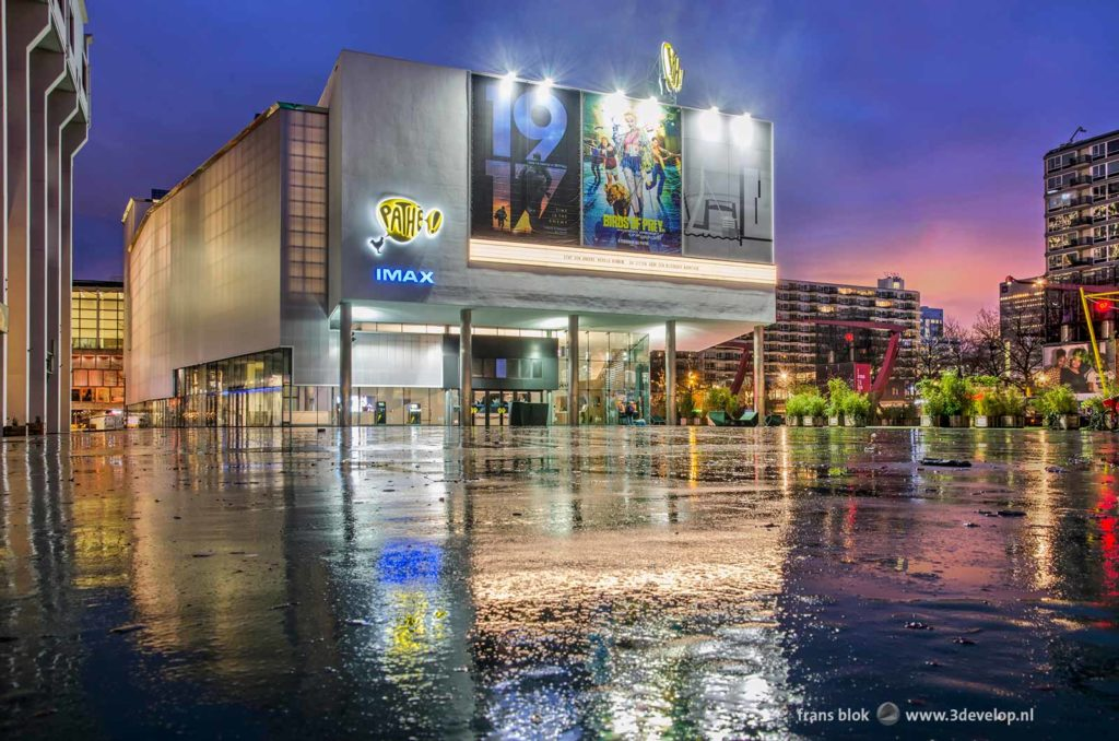 De Pathe-bioscoop met filmreclames weerspiegelt in het natte oppervlak van het Schouwburgplein in Rotterdam tijdens het krieken van de dag