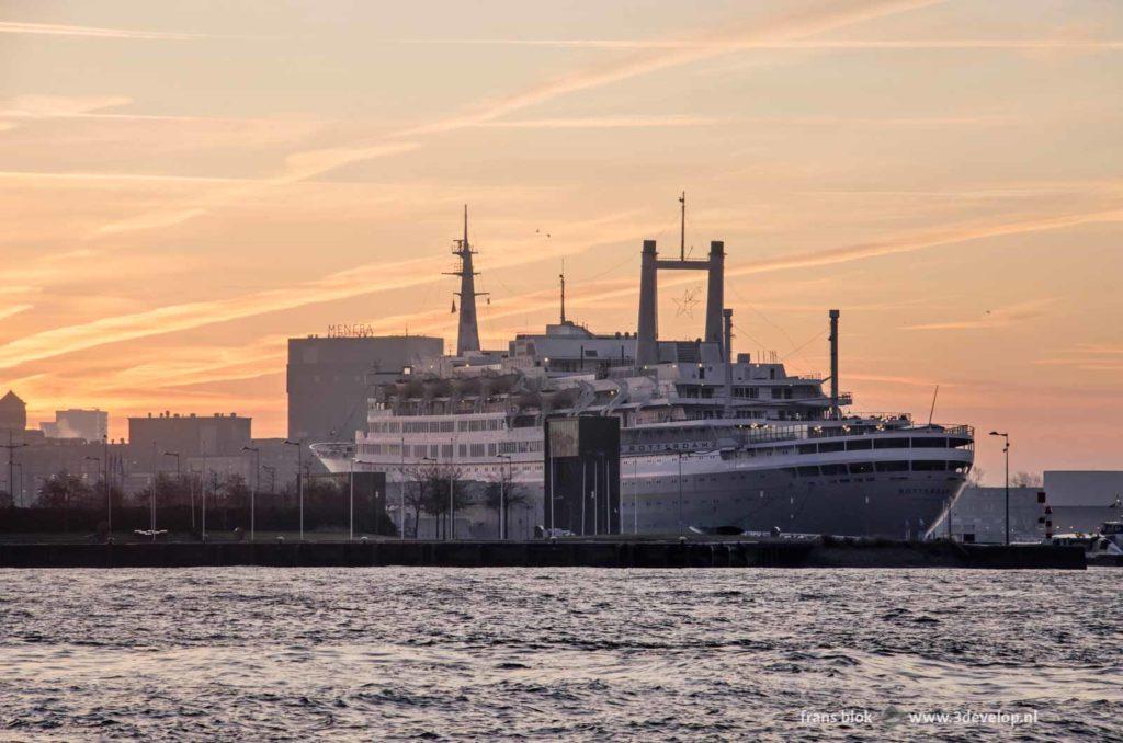Het voormalig cruiseschip SS Rotterdam, de graansilo van Meneba en de Nieuwe Maas in Rotterdam bij zonsopkomst onder een fraaie lucht met vliegtuigstrepen