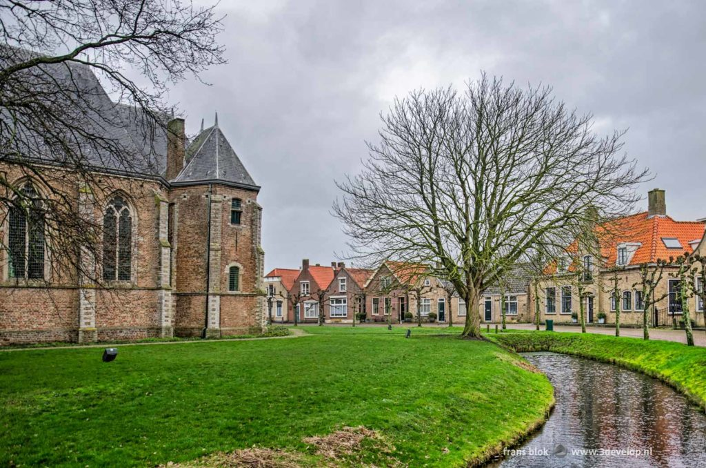 The Ring in the characteristic village of Dreischor on the Dutch island of Schouwen-Duiveland, with in the middle the church and around it a green garden, a narrow canal and a street with historic houses