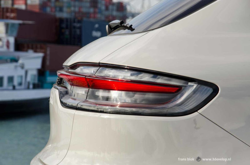 Beautifully designed rear light of a Porsche Macan turbo, against a industrial background of containers at Maasvlakte in Rotterdam