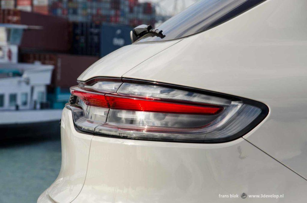 Fraai vormgegeven achterlicht van de Porsche Macan Turbo, tegen een achtergrond van containers op de Maasvlakte in Rotterdam