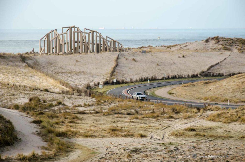 Porsche Macan Turbo in de bocht op de Maasvlakte in Rotterdam ter hoogte van kunstwerk De Zandwacht