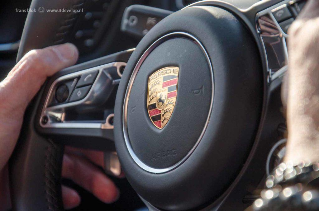 Twee handen aan het stuur van een Porsche