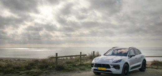 Silver grey Porsche Macan Turbo parked at Maasvlakte near Rotterdam with the sea and a spectacular cloudy sky in the background