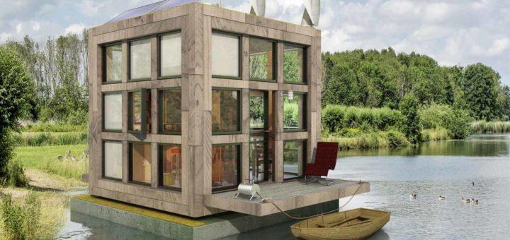 Het Blokje van Blok, een drijvend tiny house in een groene omgeving met bos, water, struiken, gras, riet en ganzen