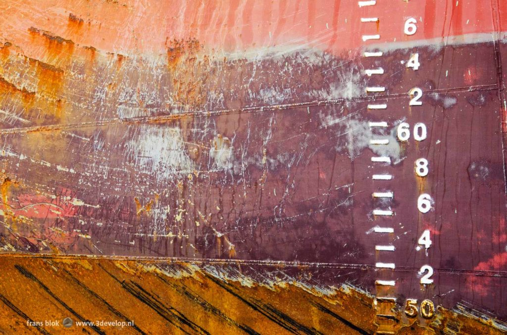 Secttion of a rusty ship's hull in colors red and brown with welding joints and draughtmarks