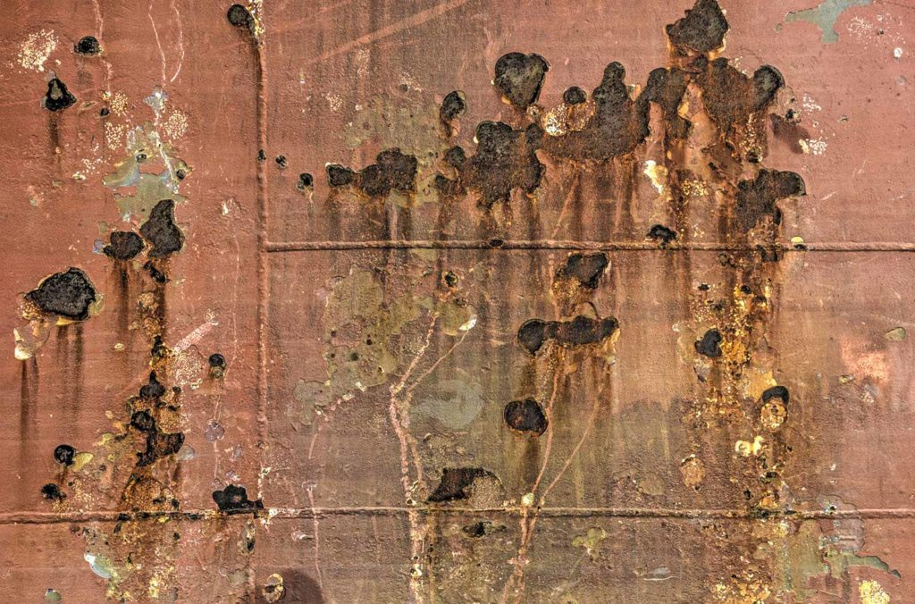 Old reddish brown ship's hull with rust and other damage