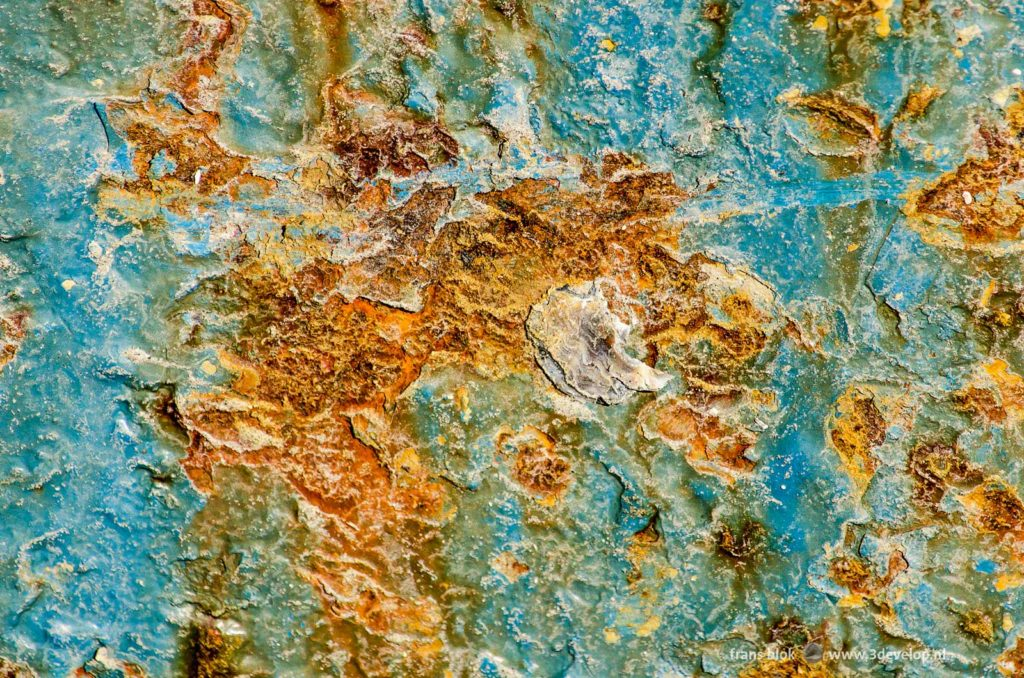 Detail of a light blue steel ship's hull that is heavily damaged by rust