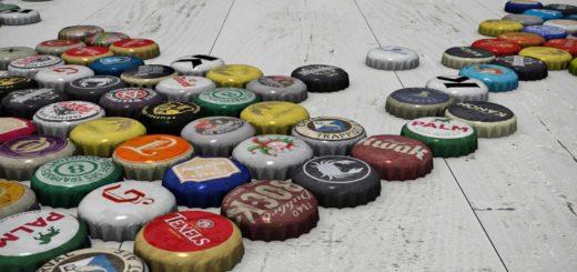 Close-up van een groot aantal kroonkurken van Belgische en Nederlandse bieren op een witte houten vloer die samen een wereldkaart vormen