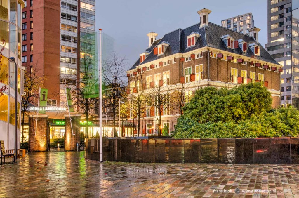 17th century Schielandshuis building in downtown Rotterdam surrounded by modern highrise seen from Coolsingel boulevard on a rainy evening