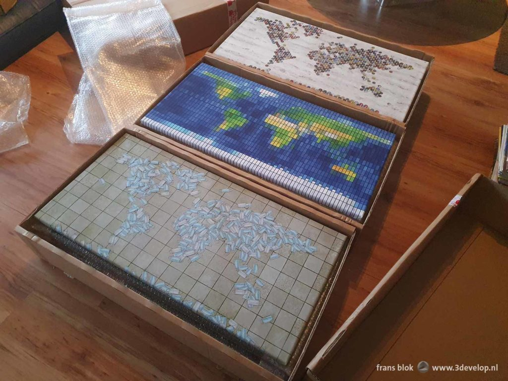 Fifteen world maps on canvas prints in three cardboard boxes, ready for an exhibition