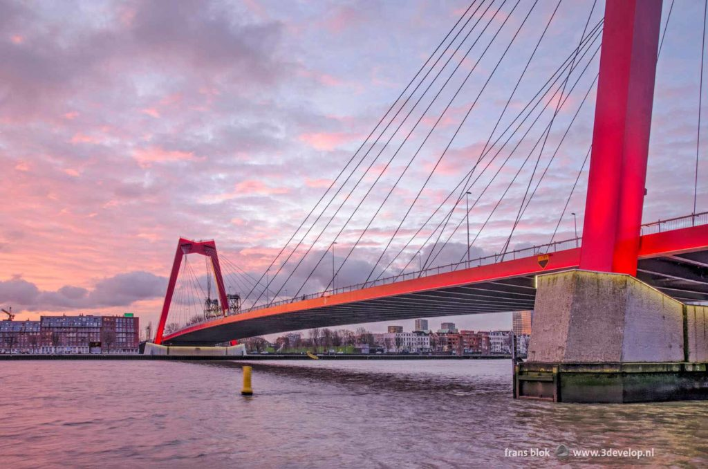 Willems Bridge, Nieuwe Maas river and Noordereiland in Rotterdam under a spectacular sky at sunrise