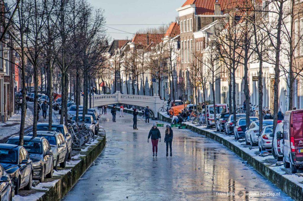 Schaatsen op het ijs aan de Voorstraat in Delft op een zonnige dag in de winter van 2021