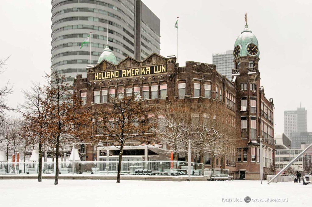 Hotel New York op de Wilhelminapier in Rotterdam omringd en bedekt door een laag vers gevallen sneeuw in de winter van 2021