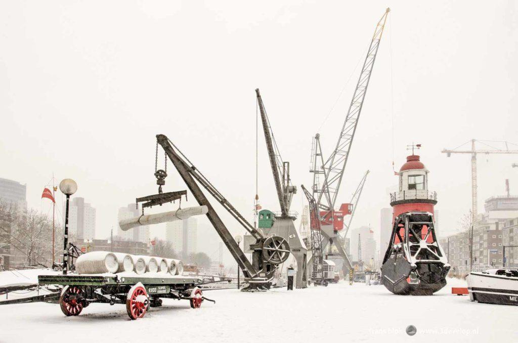 Compositie met kranen en ander historische havenobjecten in het maritiem buitenmuseum bij de Leuvehaven in Rotterdam, alles bedekt met vers gevallen sneeuw