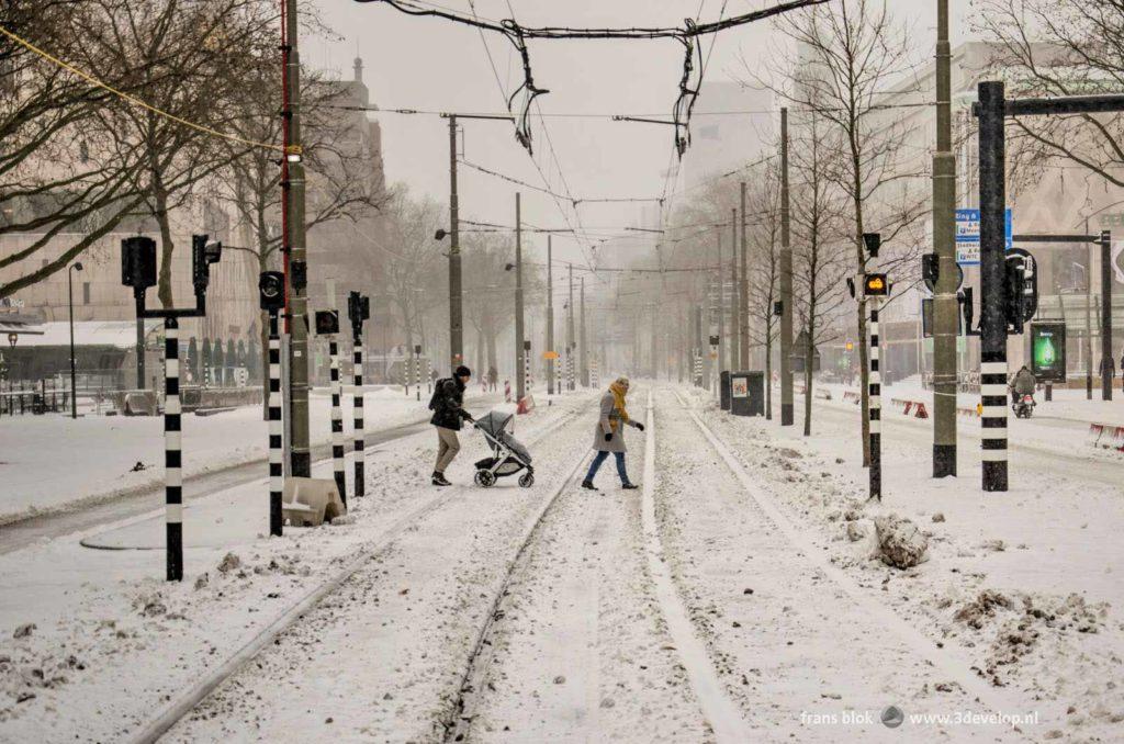 Stel met kinderwagen probeert de tramrails over te steken op de met een vers pak sneeuw bedekte Coolsingel in Rotterdam tijdens een sneeuwstorm in de winter van 2021