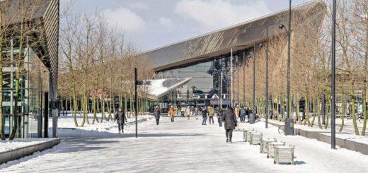 Het Kruisplein in Rotterdam bedekt met aangestampte sneeuw en op de achtergrond het Centraal Station op een zonnige dag in de winter van 2021