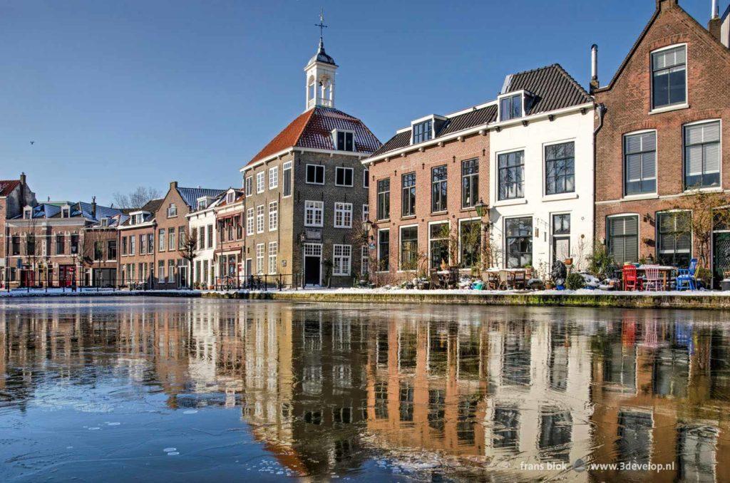 Zakkendragershuisje en andere historische panden spiegelend in het dunne ijs op de Schie in Schiedam op een zonnige dag in de winter van 2021