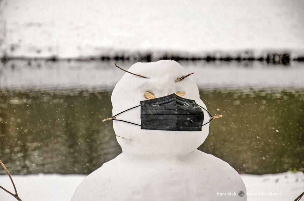 Sneeuwpop met zwart mondkapje in het Park in Rotterdam tijdens de winter van 2021