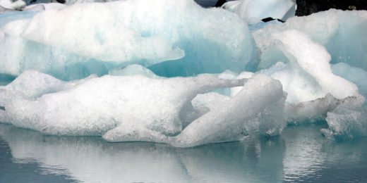 Wild shapes of ice floating in the blue water of ice lake Jokulsarlon in Iceland, under a dark sky