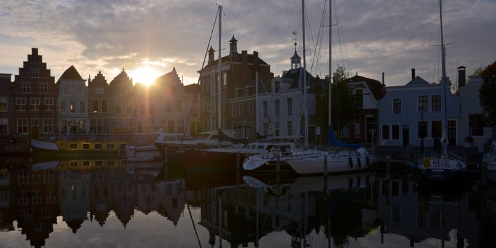 Photo of the little harbour of Goes, Zeeland, The Netherlands, with old houses, reflecting water surface and various boats, in beautiful evening light