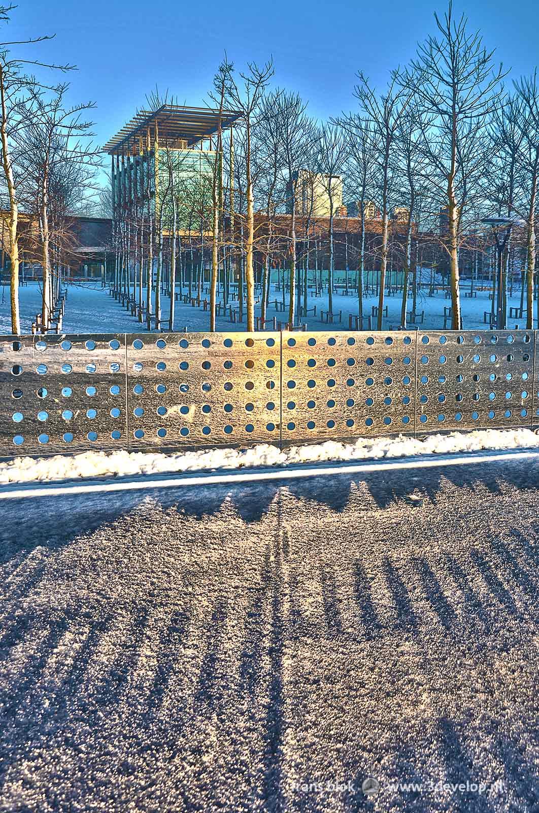 Het Museumpark en het Nieuwe Instituut in Rotterdam op een winterdag, met zonnestralen die reflecteren op een spiegelwand en terugkaatsen op het besneeuwde oppervlak van het asfaltplein