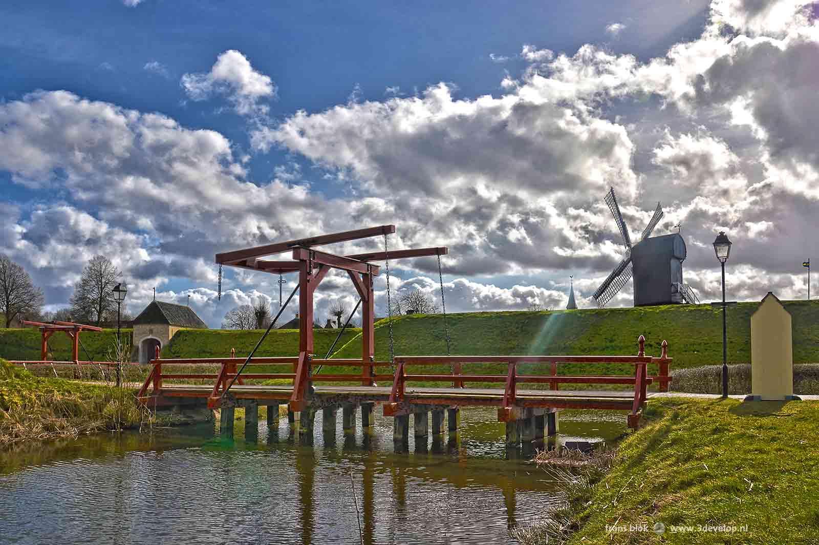 Foto van de herbouwde vesting Bourtange, met een ophaalbrug, een toegangspoort en de molen