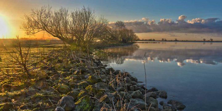 Photo of Korendijk Wetlands, the Netherlands, showing the sun rise above the banks of Haringvliet estuary