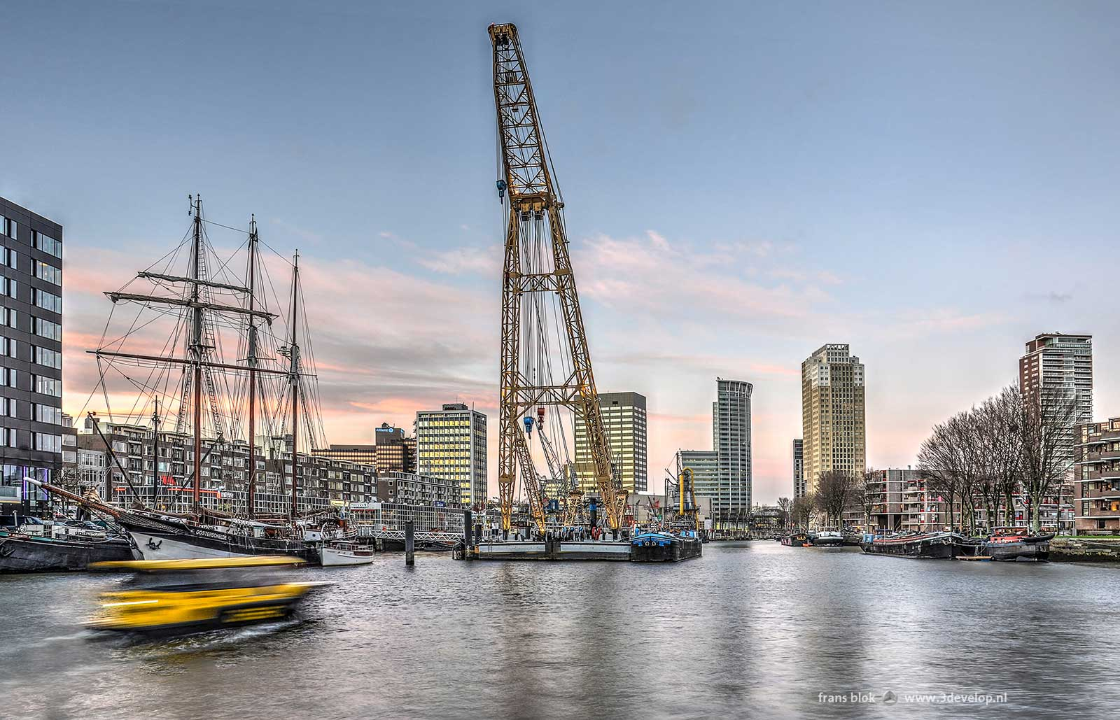 Leuve Harbour in Rotterdam not long before sunset, featuring a water taxi, a floating crane and a three-master