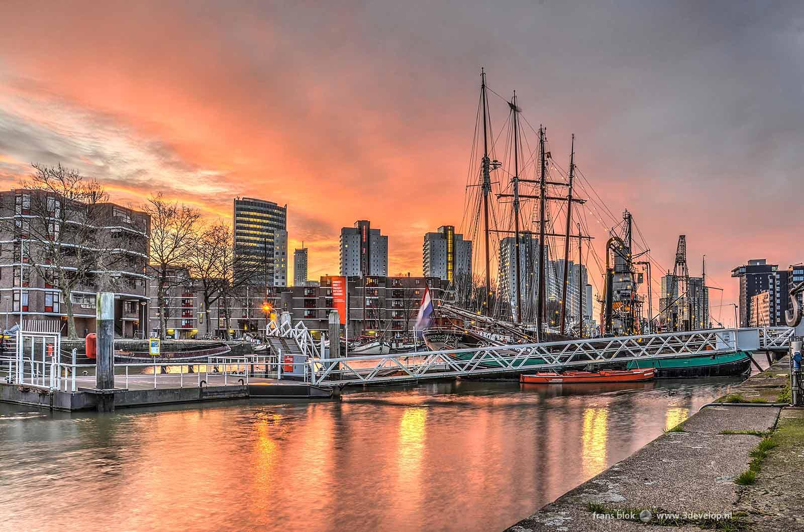 Een rode lucht bij de zonsopkomst boven de Leuvehaven met het Maritiem Buitenmuseum in Rotterdam