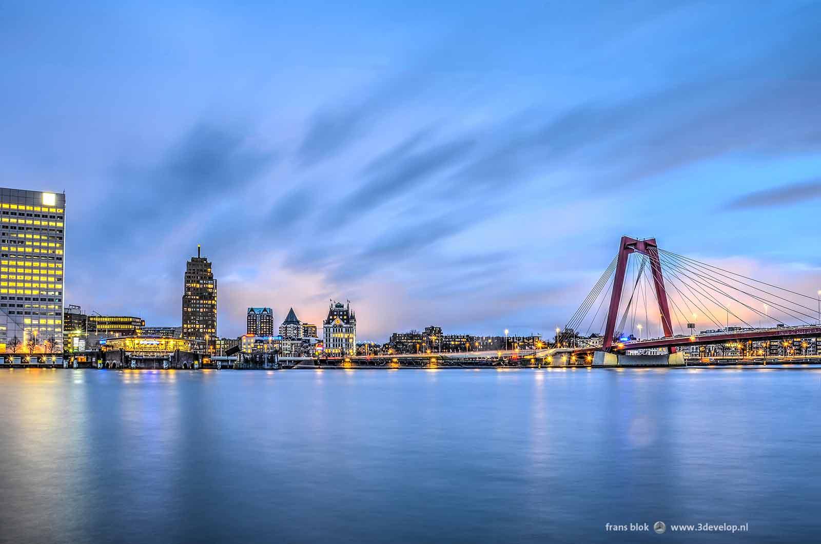 Rood-blauw-paarse lucht tijdens de zonsopkomst boven de Nieuwe Maas in Rotterdam, met het deel van de Boompjes tussen Willemswerf en Willemsbrug