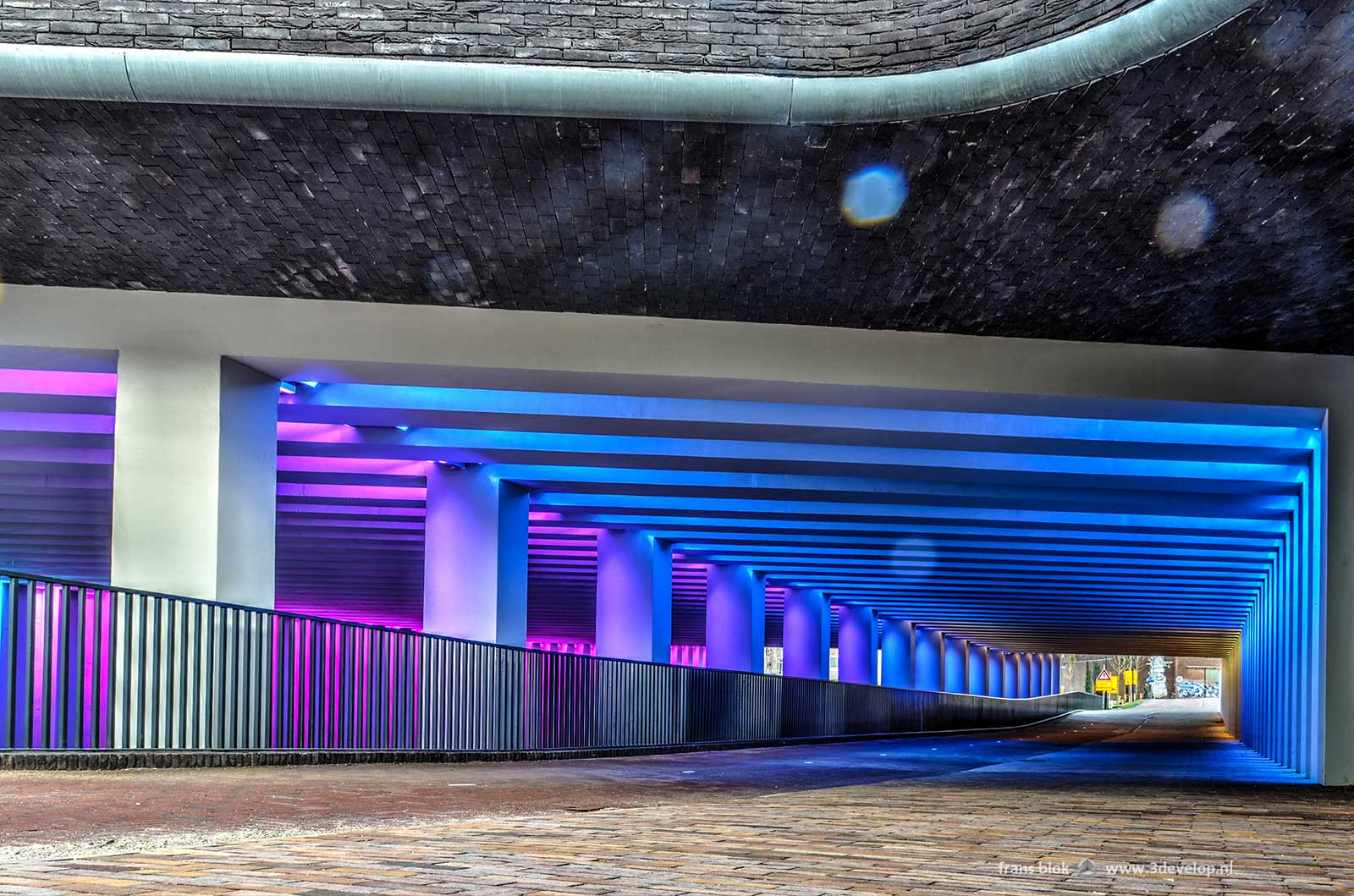 Photo of the entrance of the Marstunnel in Zutphen from the side of the city centre, with the light art by Herman Kuijer in blue and purple
