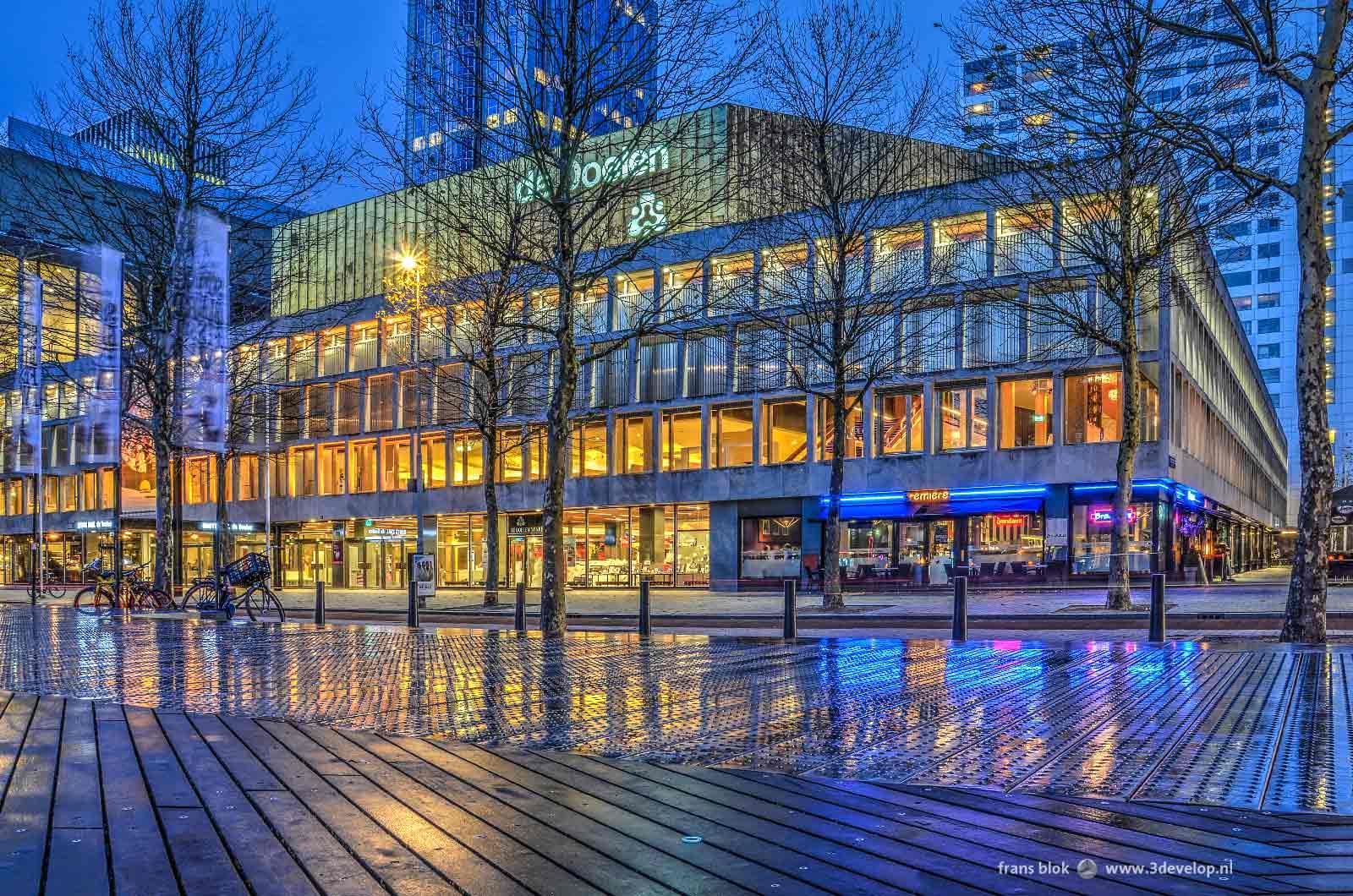 Avondbeeld van concert- en congresgebouw de Doelen in Rotterdam, reflecterend in het vochtige staal en hout van het Schouwburgplein