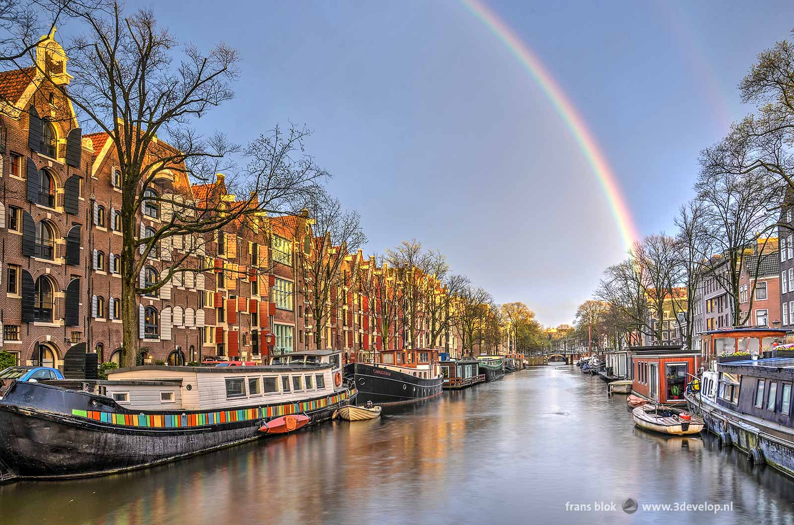 A rainbow seen from a bridge over the Brouwersgracht in Amsterdam, flanked by houseboats while the last raindrops are splashing in the water