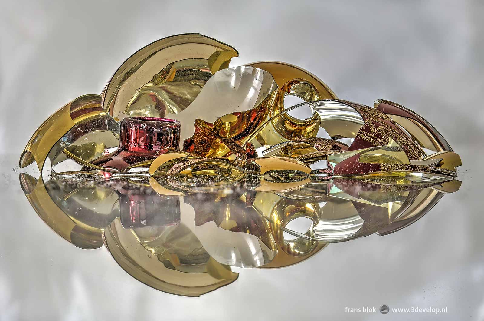Compositie met scherven van een rode en een goudkleurige kerstbal op een spiegel, gezien vanaf een laag standpunt.
