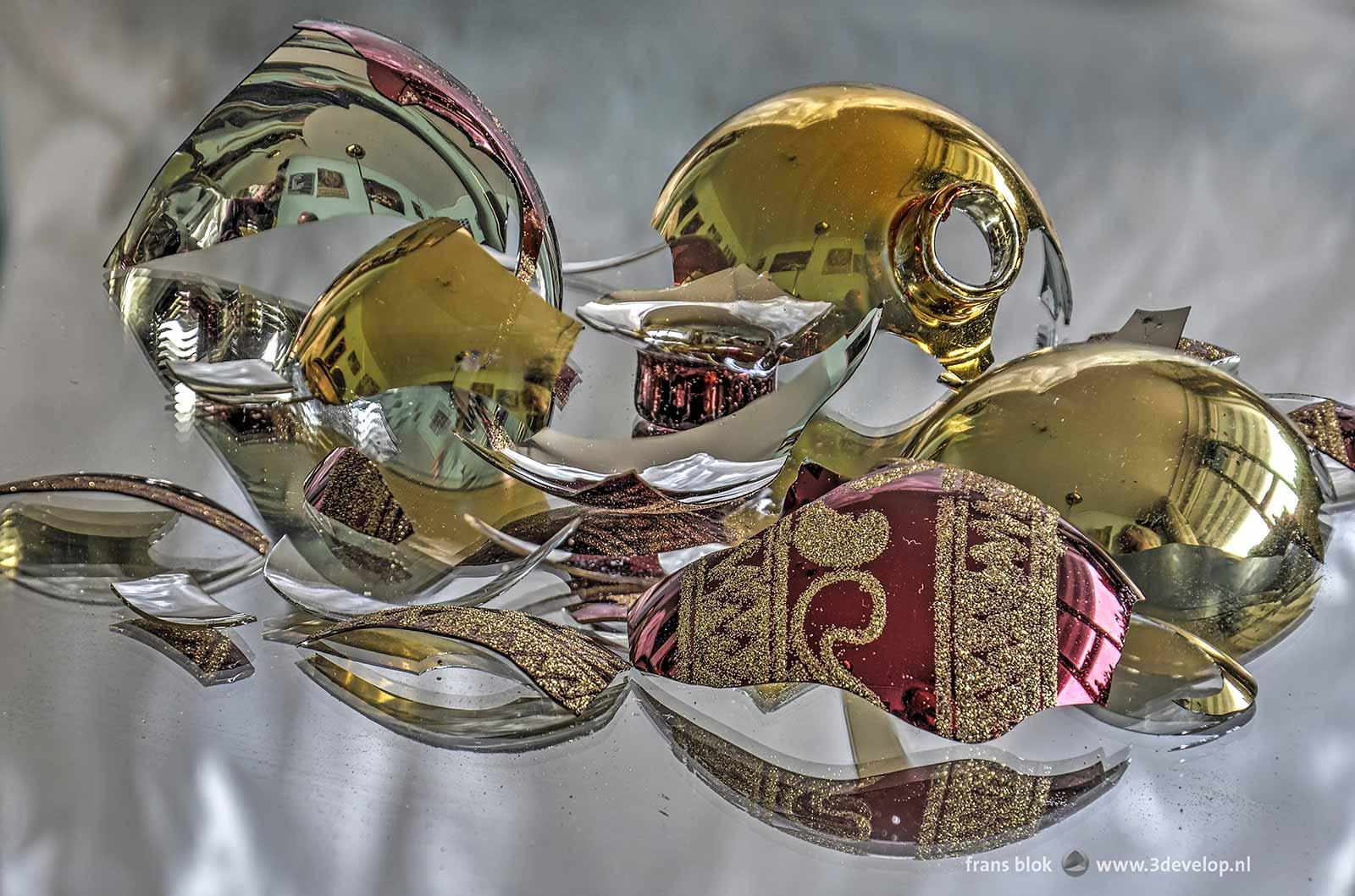 Scherven van een rode en een goudkleurige kerstbal, gerangschikt op een spiegel.