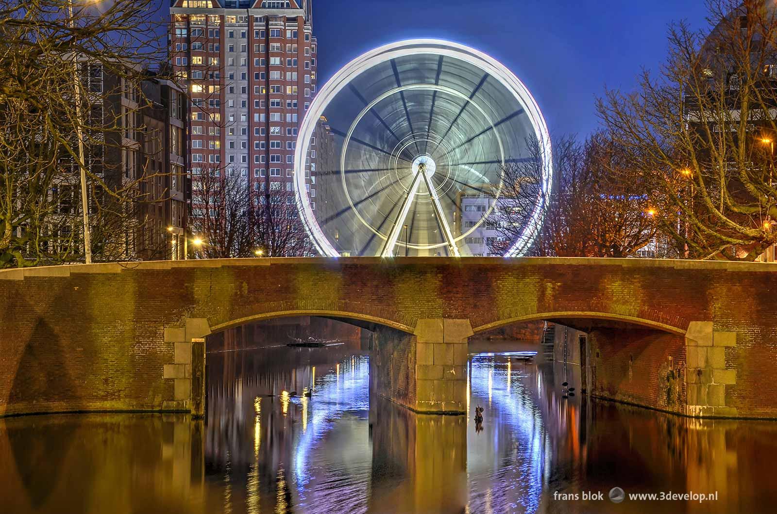 Reuzenrad The View in Rotterdam, spiegelend in de Steigergracht, met op de voorgrond de brug in de Keizerstraat