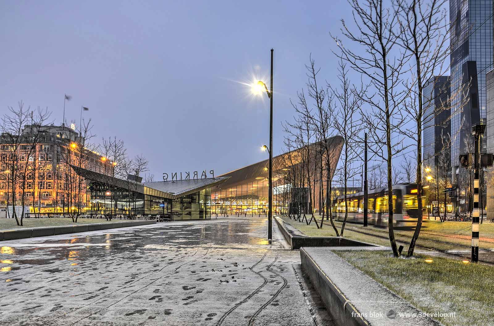 Winters beeld van het centraal station in Rotterdam in de vroege ochtend, met sneeuw en ijzel op straat en een voorbijkomende tram.